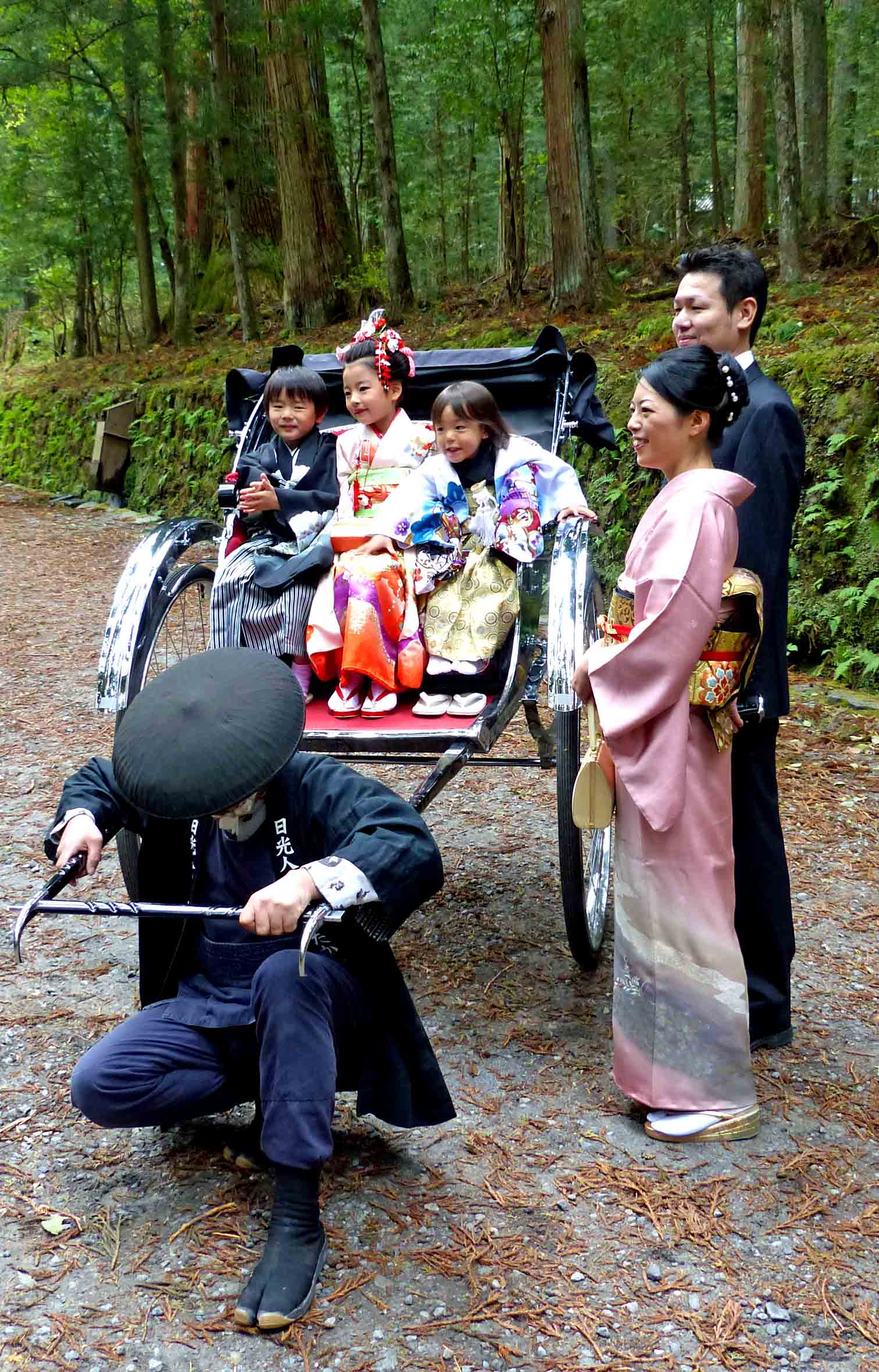 Japanese children in a rickshaw and parents standing nearby