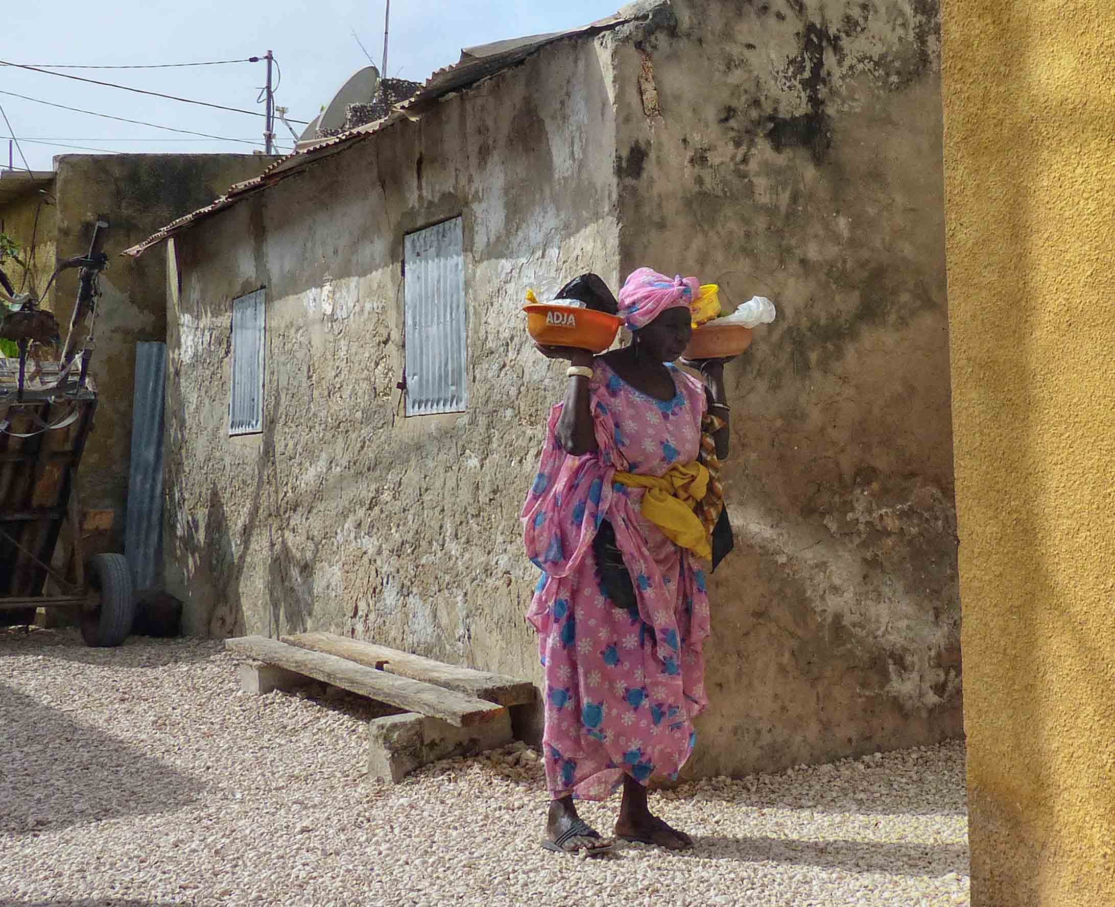 Lady in pink dress carrying bowls