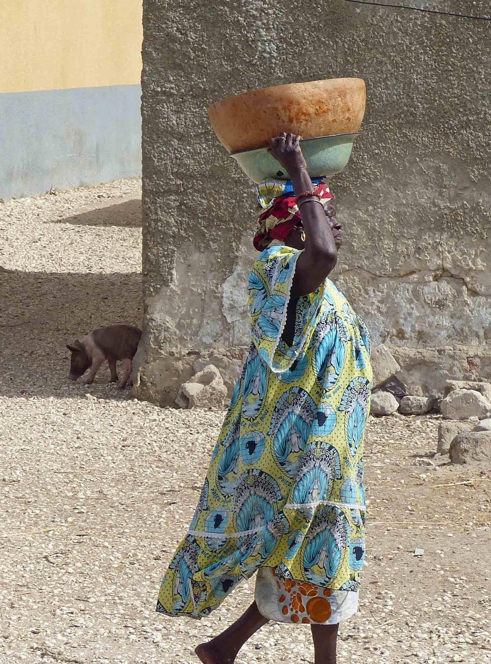Woman carrying two bowls on her head