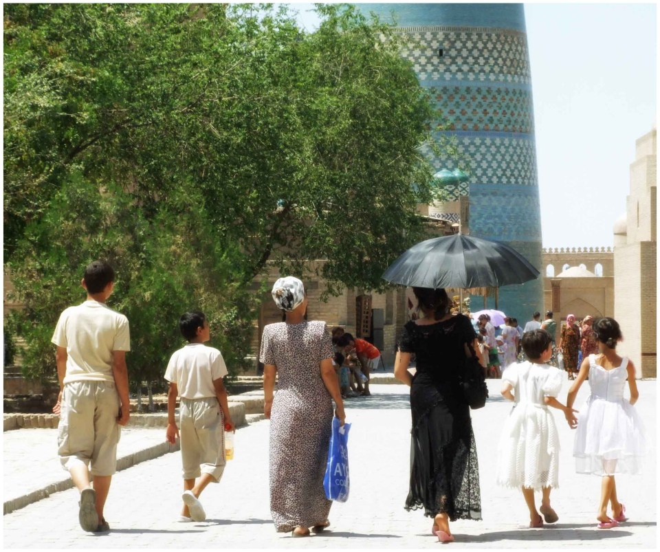 Two women, four children on a street by a blue minaret