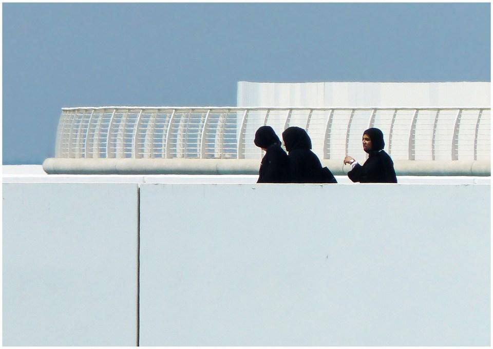 Three ladies in black hijabs on a white bridge
