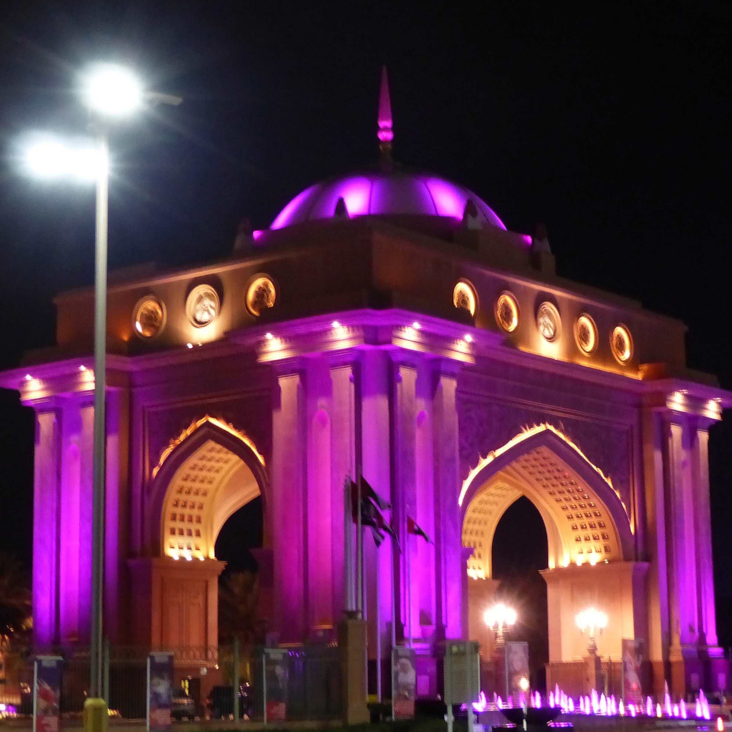 Ornate gatehouse illuminated purple at night
