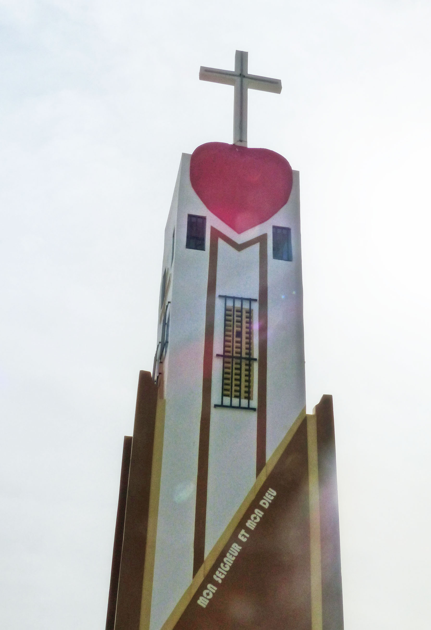 Tall white tower topped with red heart and cross