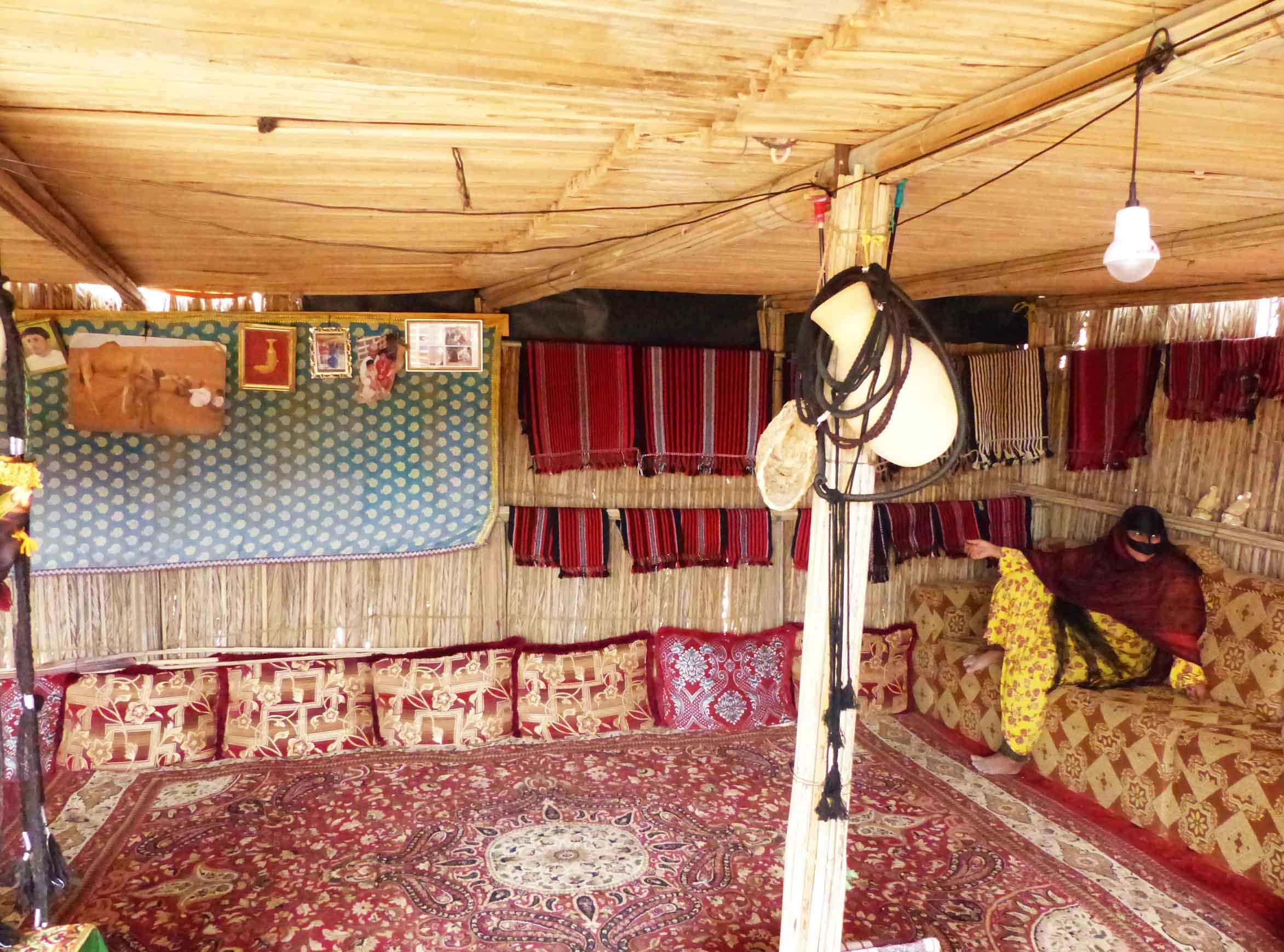 Inside a home of sticks, with red carpet and lady sitting