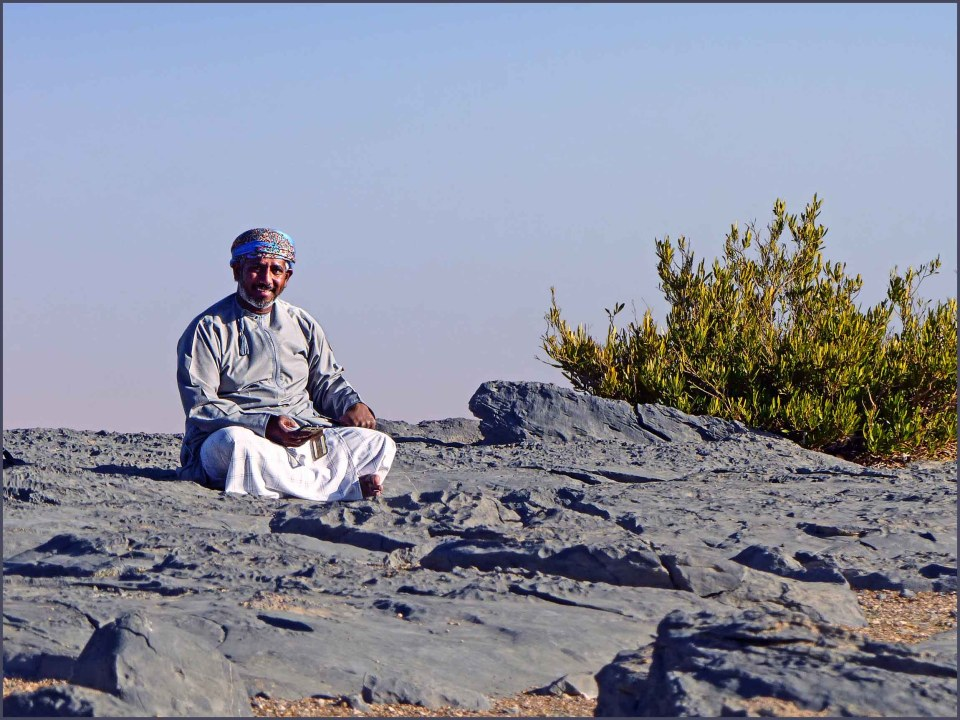 Man in Arab dress sitting on rocks