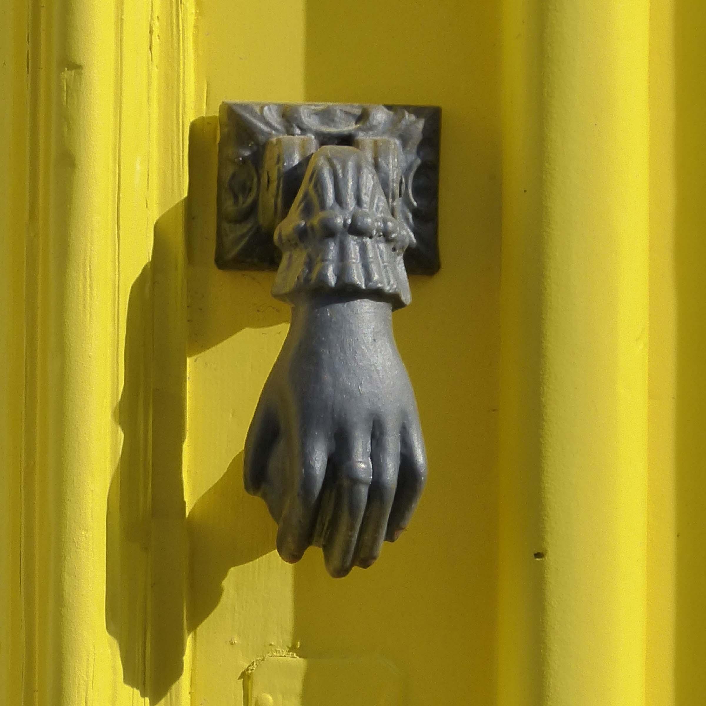 Yellow door with hand-shaped knocker