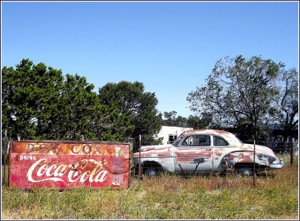 Old cola advert and rusting car
