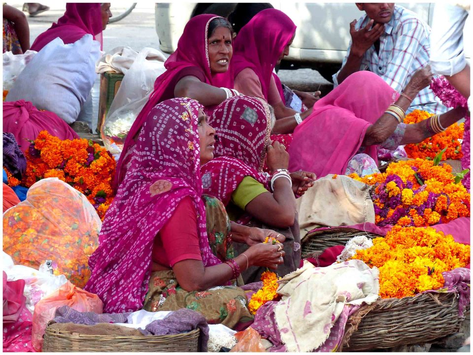 Group of ladies in pink saris with baskets of flowers