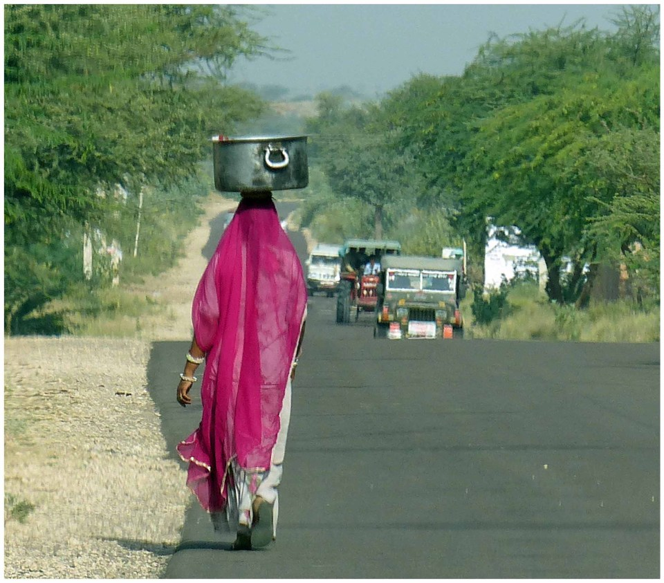 Lady in pink sari walking on road with large tin pot on her head
