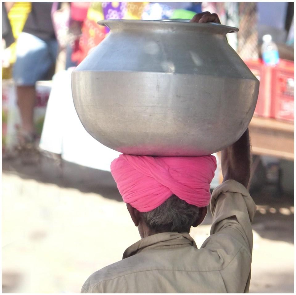 Man in pink turban with tin pot on his head