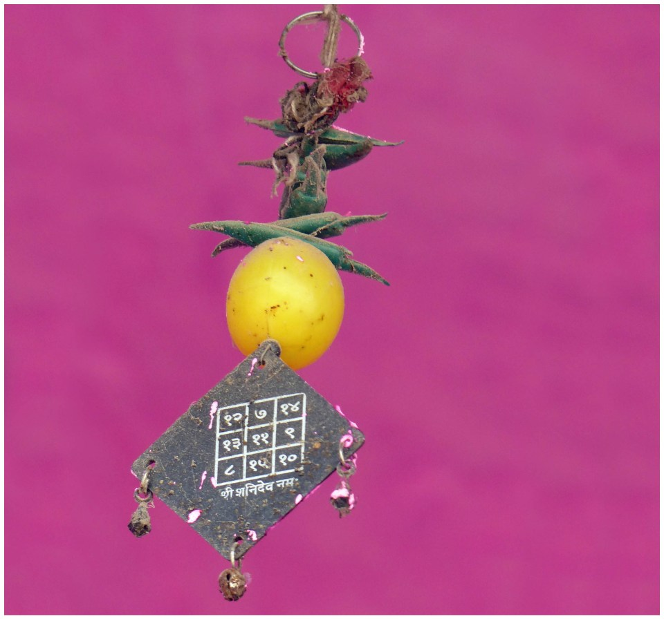 Charm hanging in front of vivid pink wall