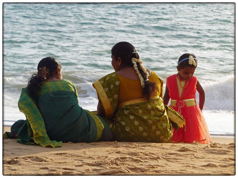 Two ladies in saris and small girl sitting on a beach