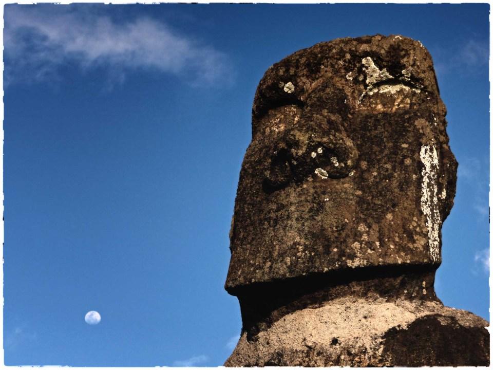 Large stone head against deep blue sky with moon
