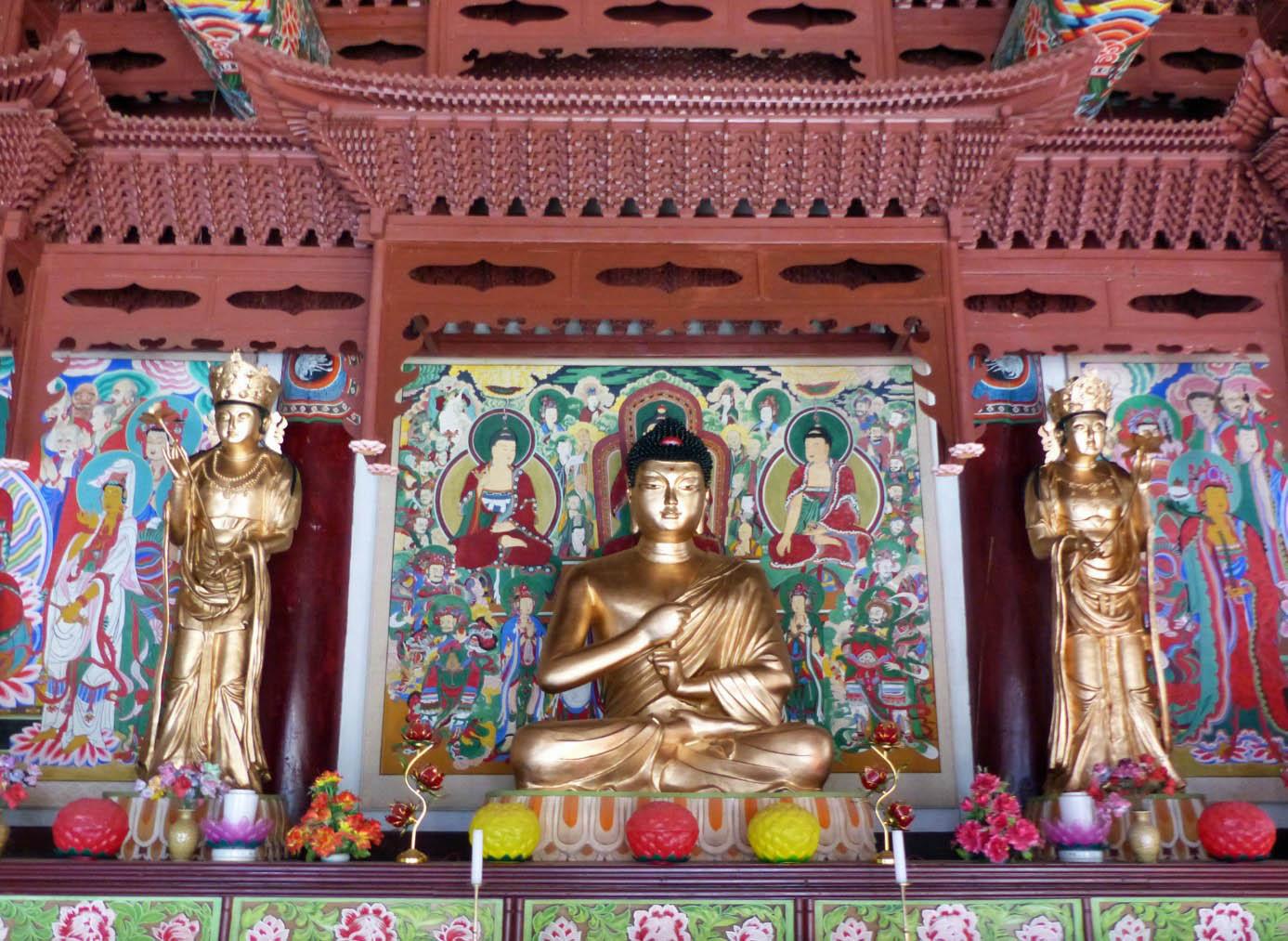 Three gold Buddhas om an altar