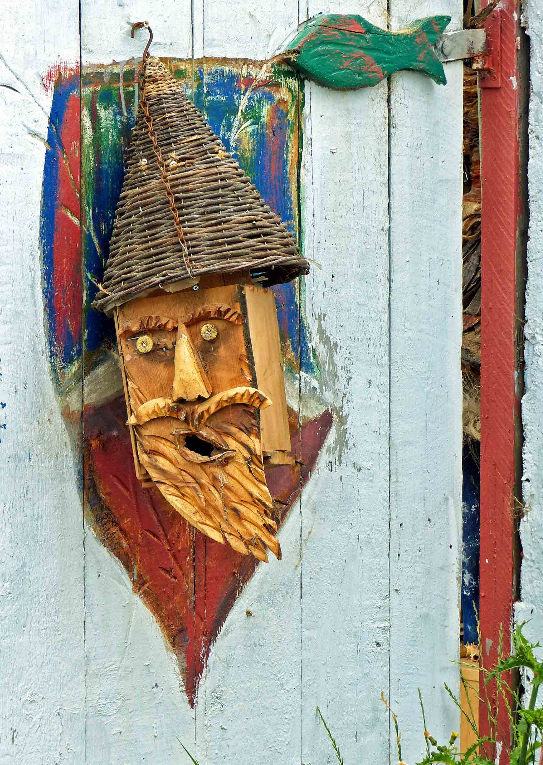 Carved wooden face hanging on a gate