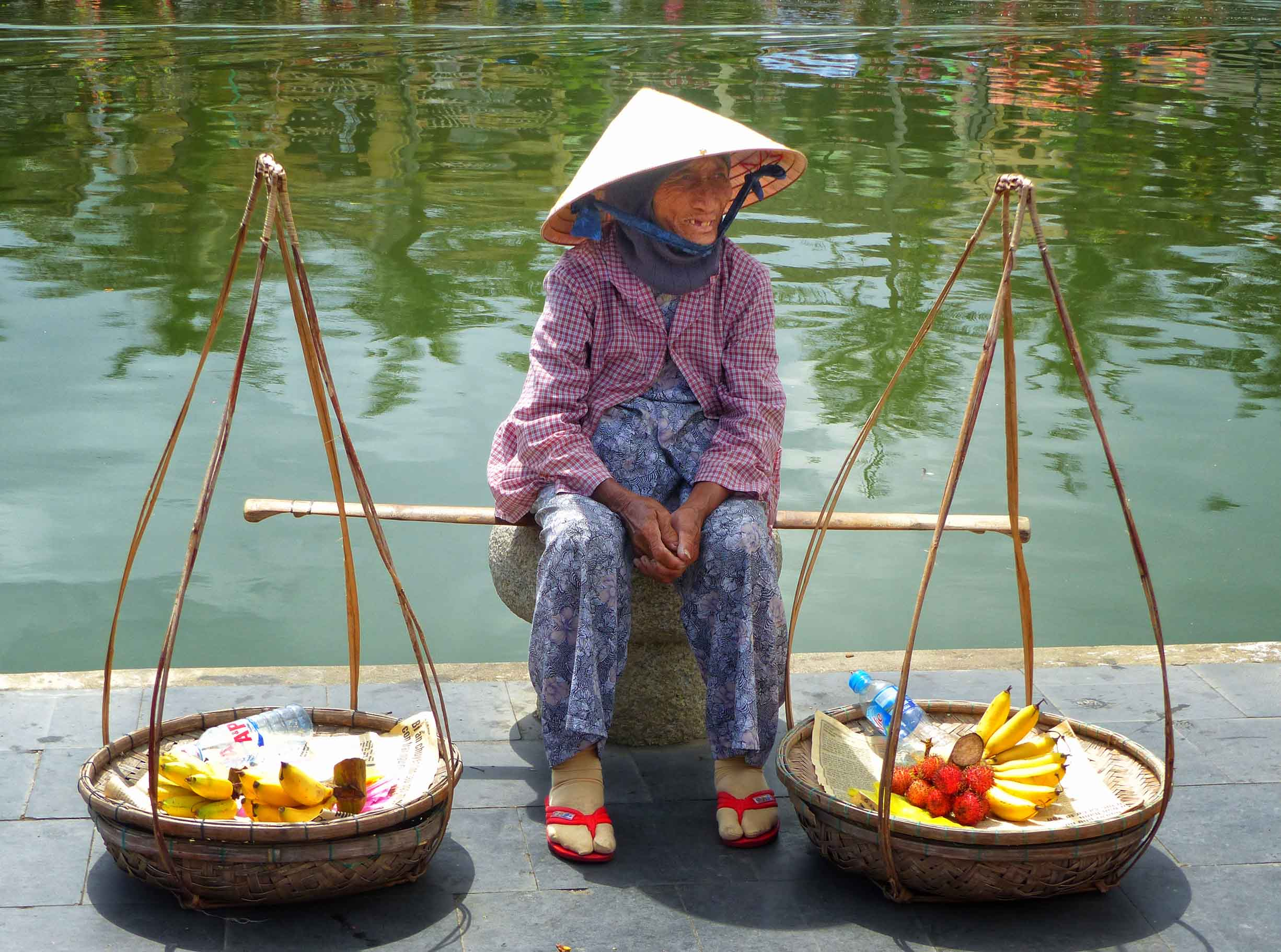 Old lady in conical hat with traditional baskets on yoke