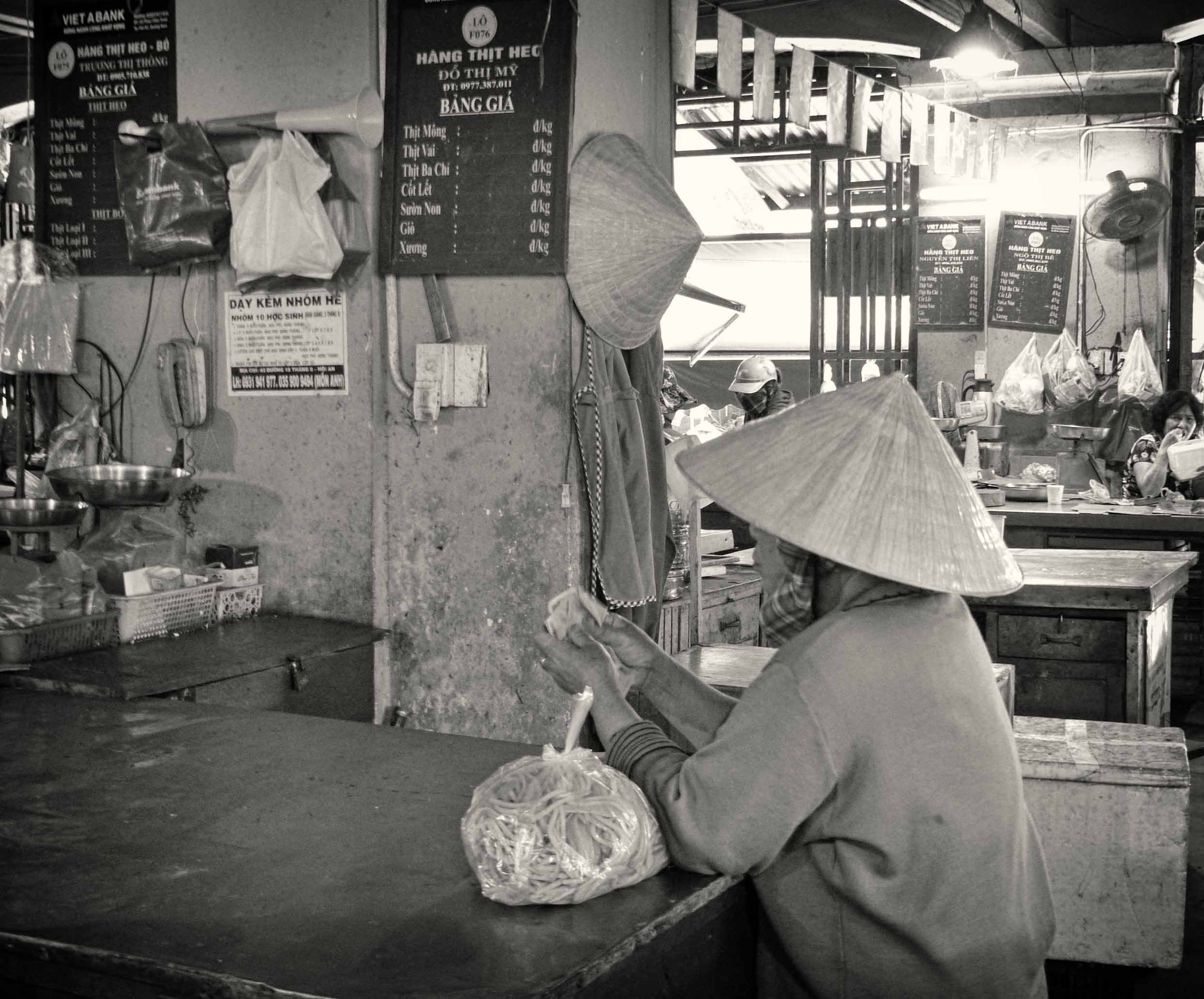 Lady in conical hat sitting at a table in a market