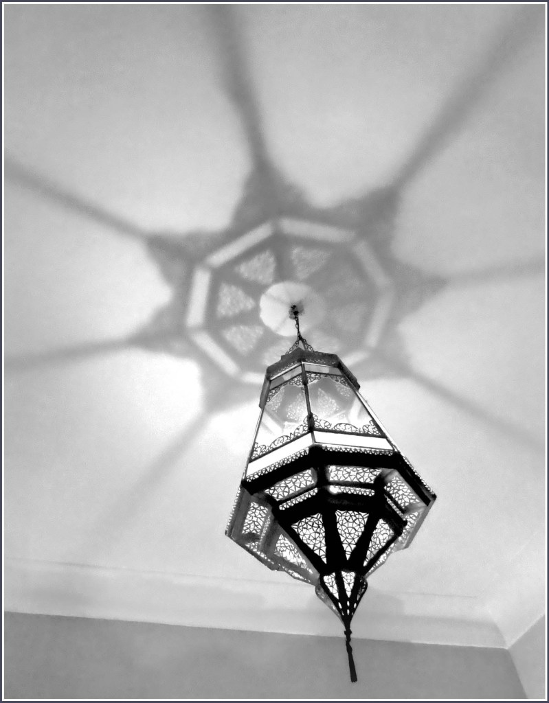 Black and white photo of delicate metal lamp hanging from ceiling