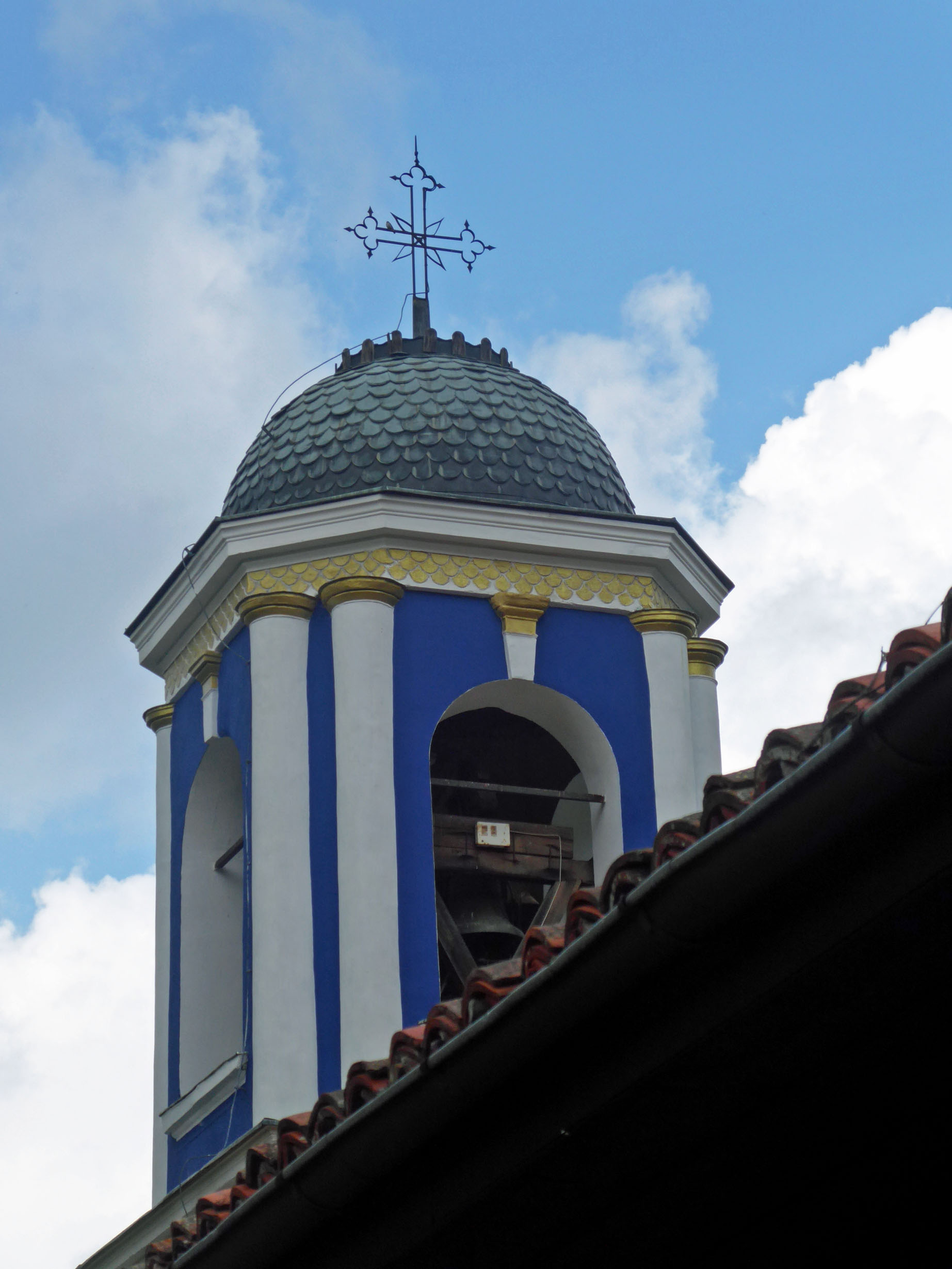 Blue and white tower with bells and domed roof