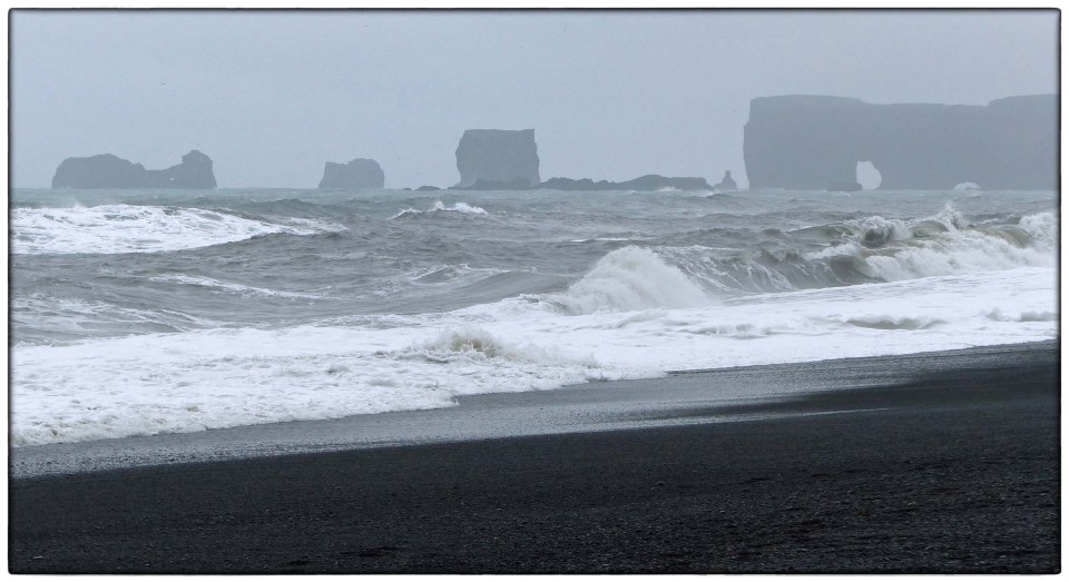 Black sand, grey waves and stone stacks
