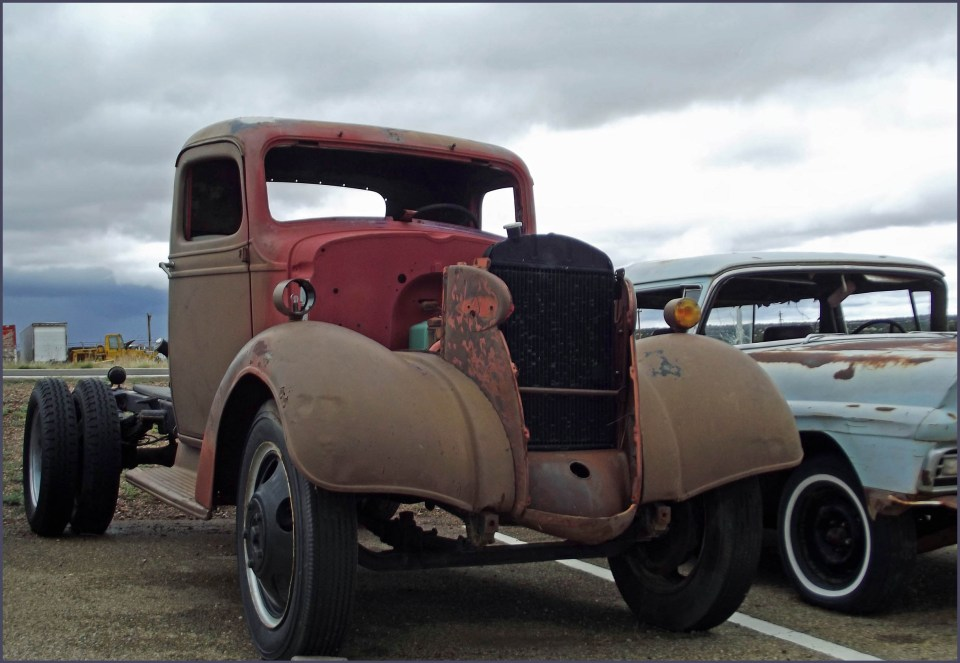 Rusting truck next to a rusting old car