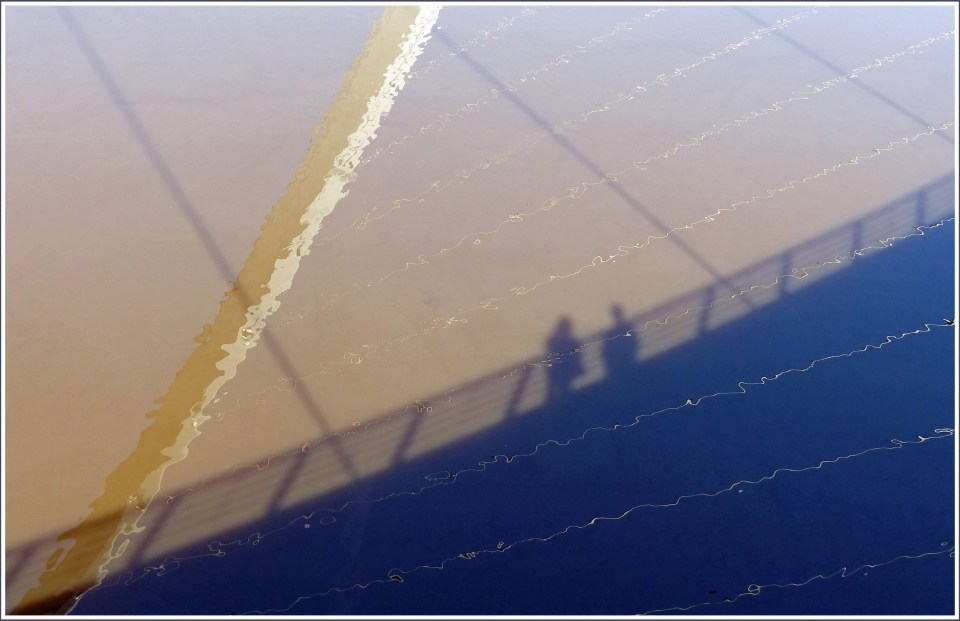 Shadow on water of couple standing on a bridge