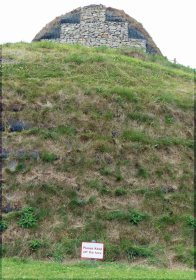Grassy slope with stones at top