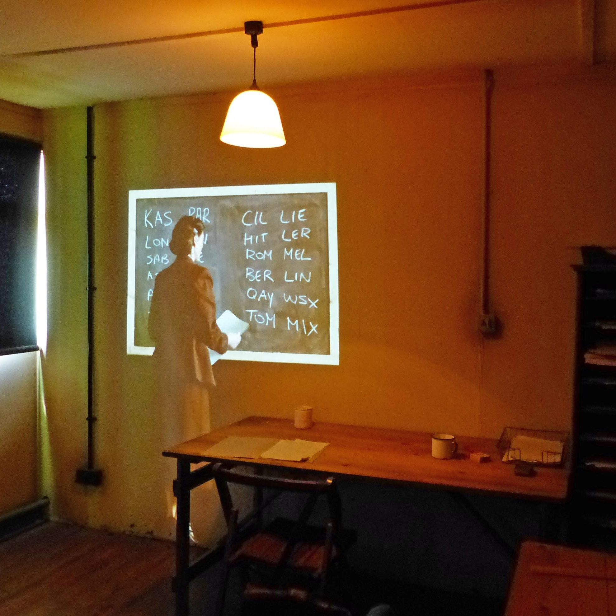 Projection on a wall of a lady writing on blackboard