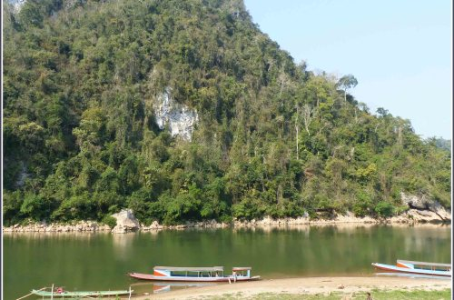 River with small boats and rocky cliff