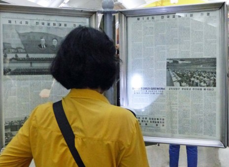 Lady in yellow blouse reading newspaper on stand