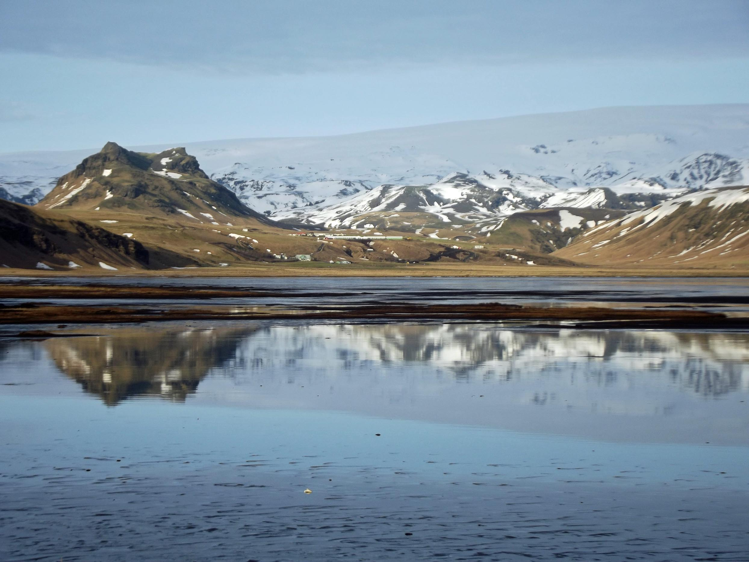 Snowy mountains reflected in still water