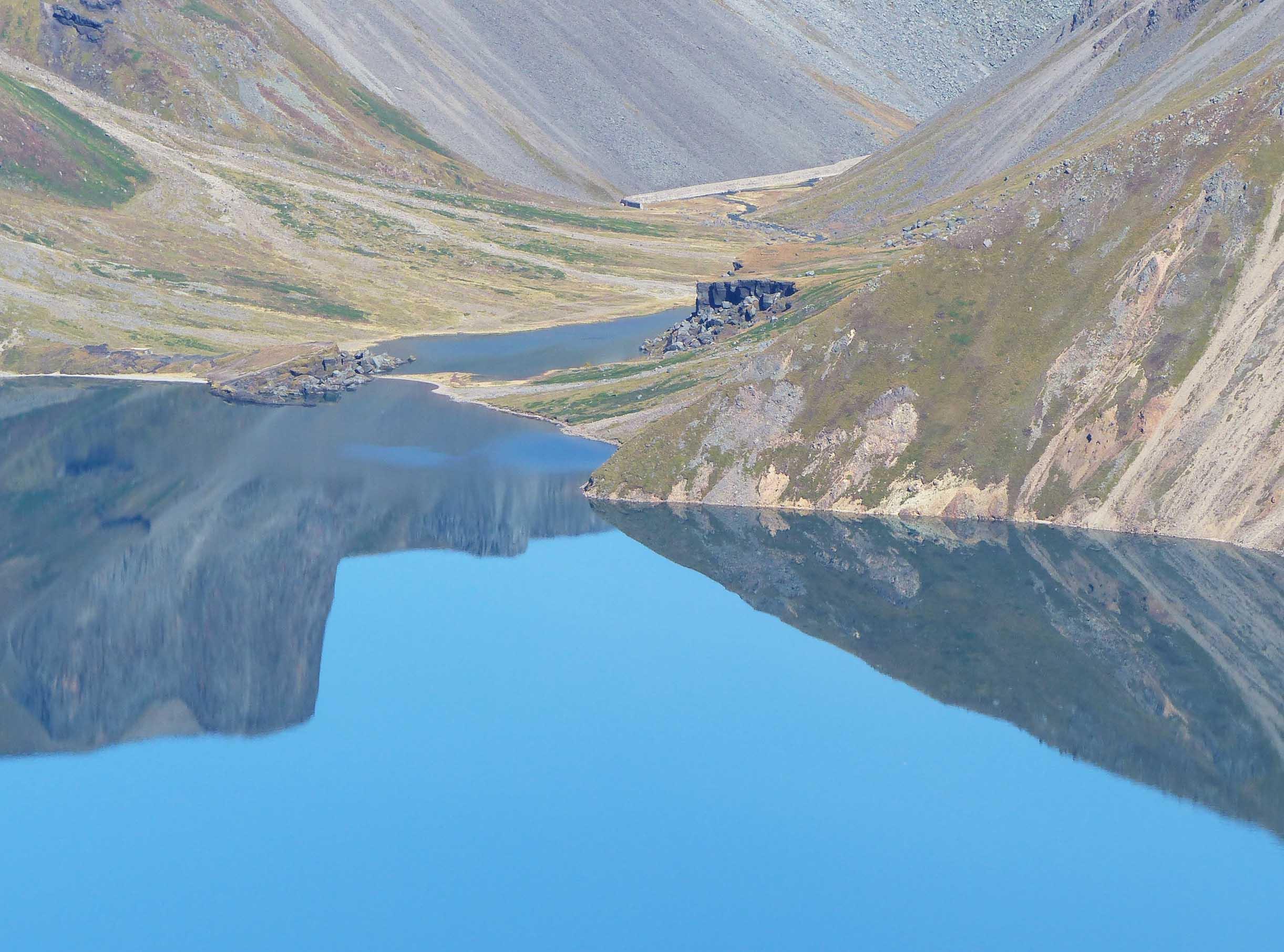 Hillside reflected in still water