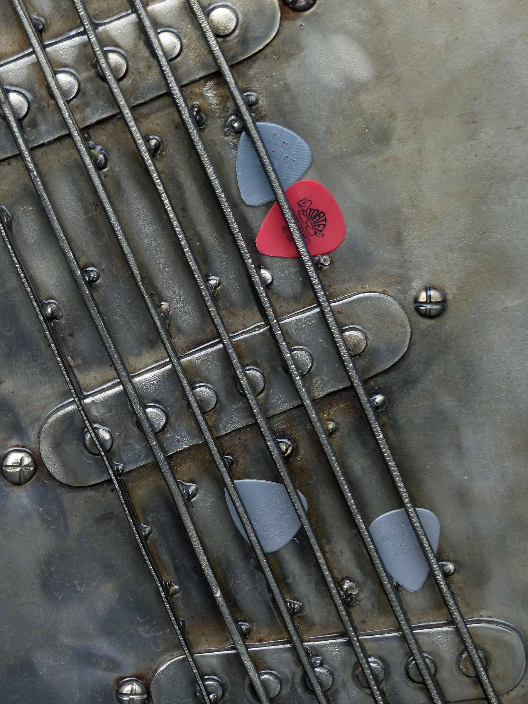 Metal sculpture of guitar strings with plastic plectrums