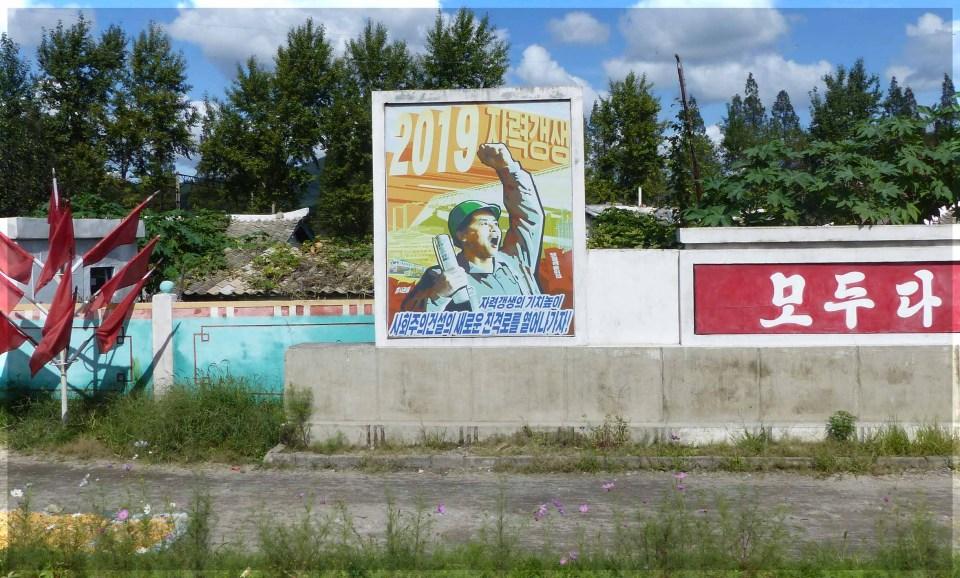 Large poster depicting man in hard hat waving arm