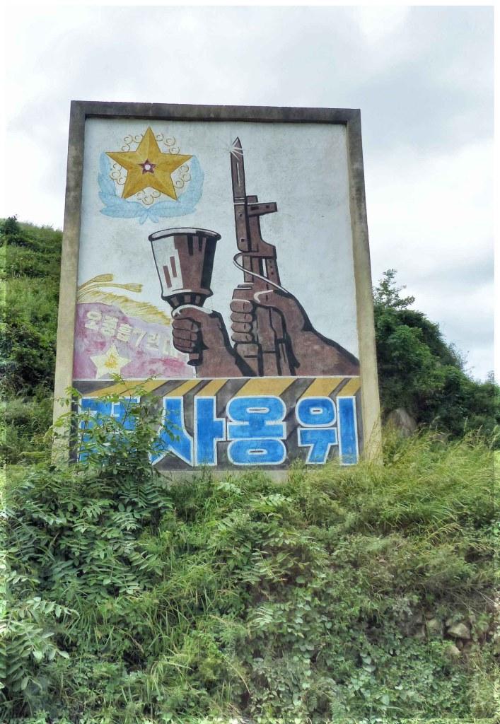 Large poster depicting hand holding gun