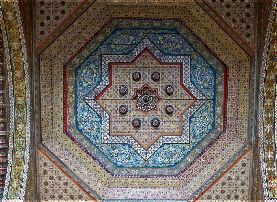 Looking up at ornate ceiling painted in blues, reds and cream