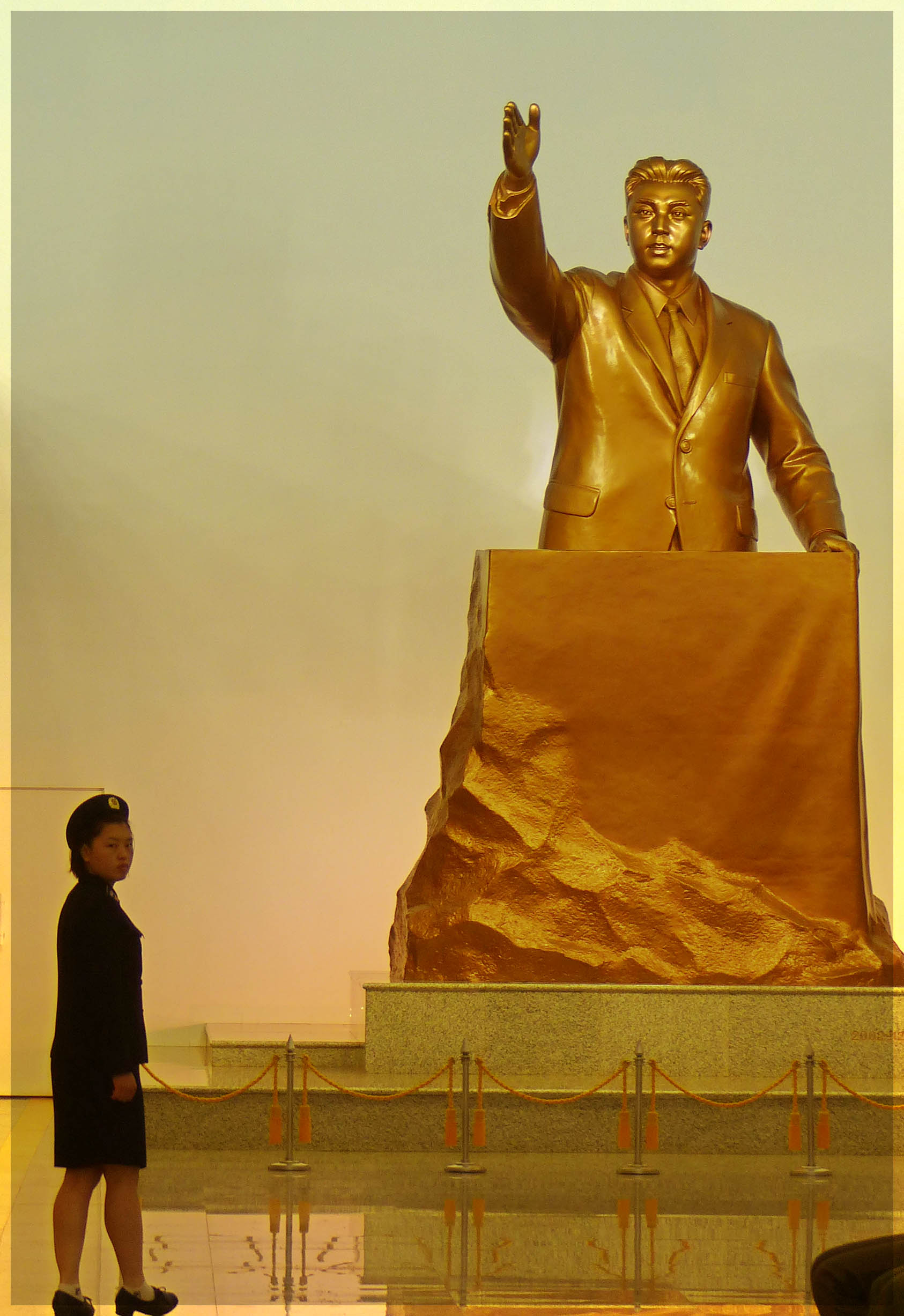 Huge gold statue of man at a podium and young lady in uniform in front
