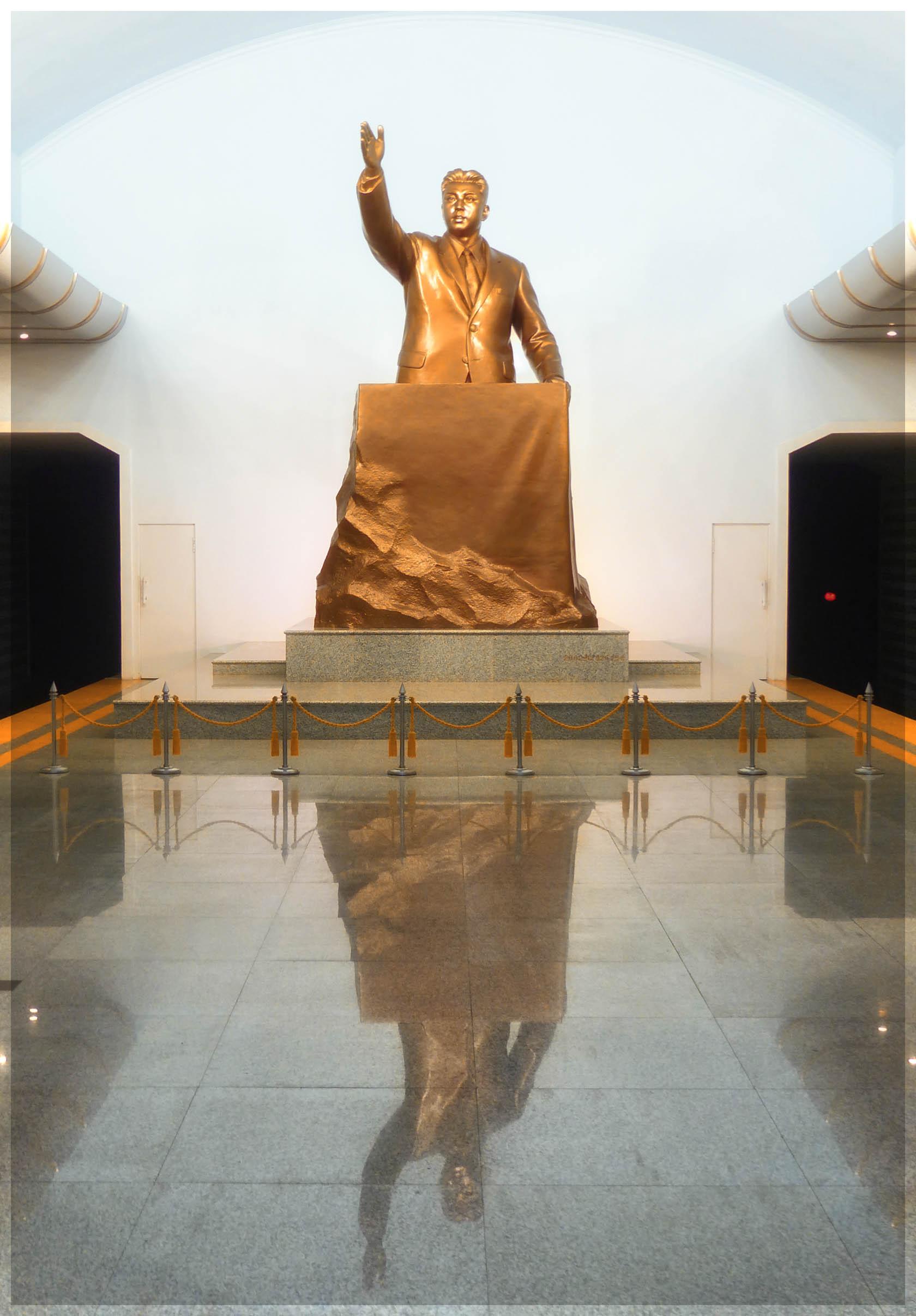 Huge gold statue of man giving a speech