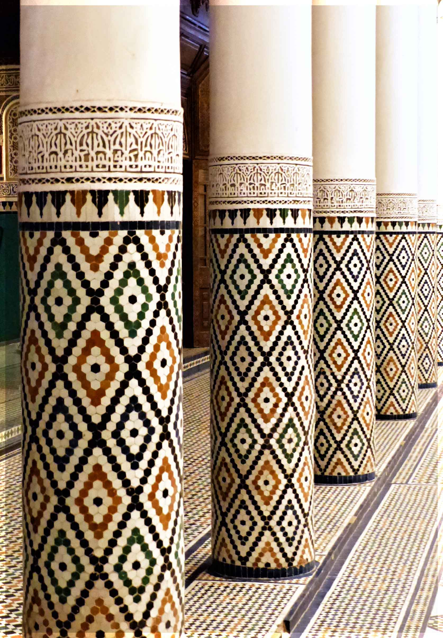 Round columns decorated with small tan, white and dark green tiles
