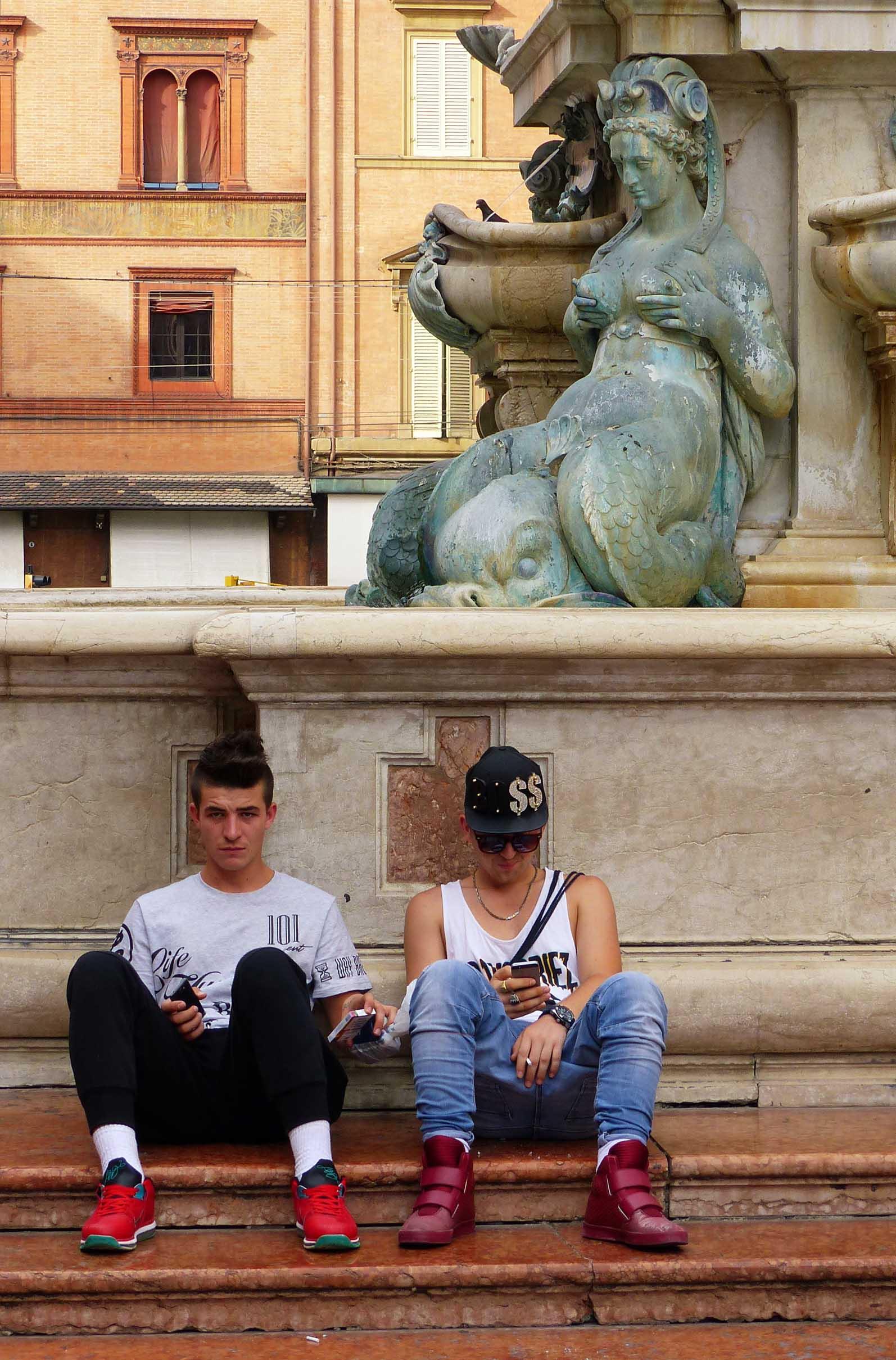 Two teenage boys sitting on steps below a fountain
