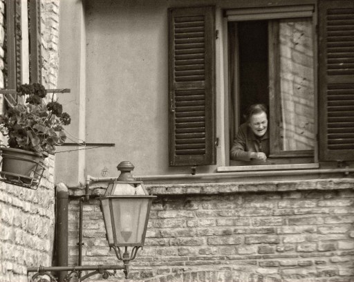 Lady looking out of a shuttered window