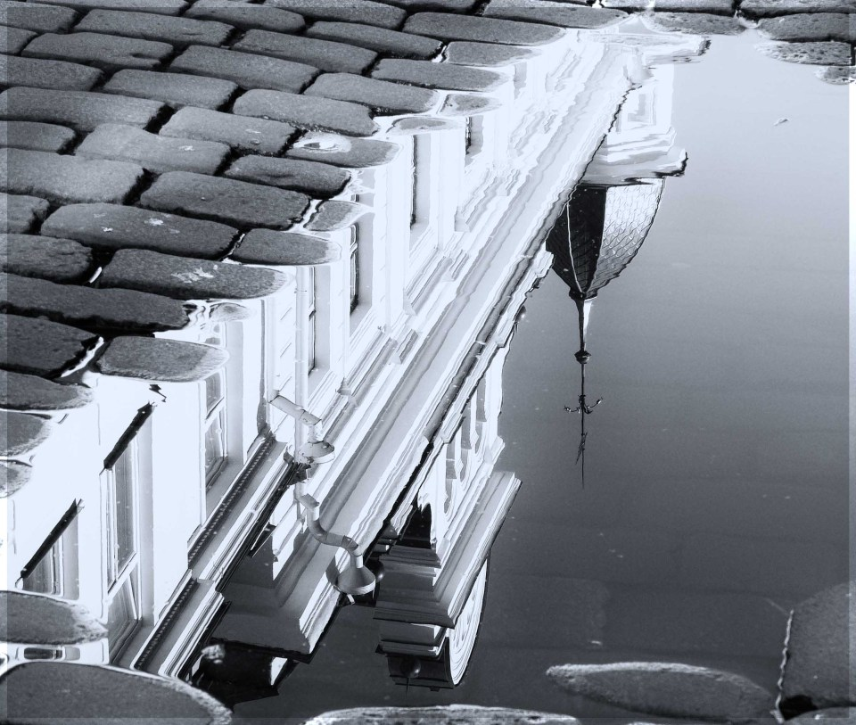 Building reflected upside down in a puddle on cobbled stones