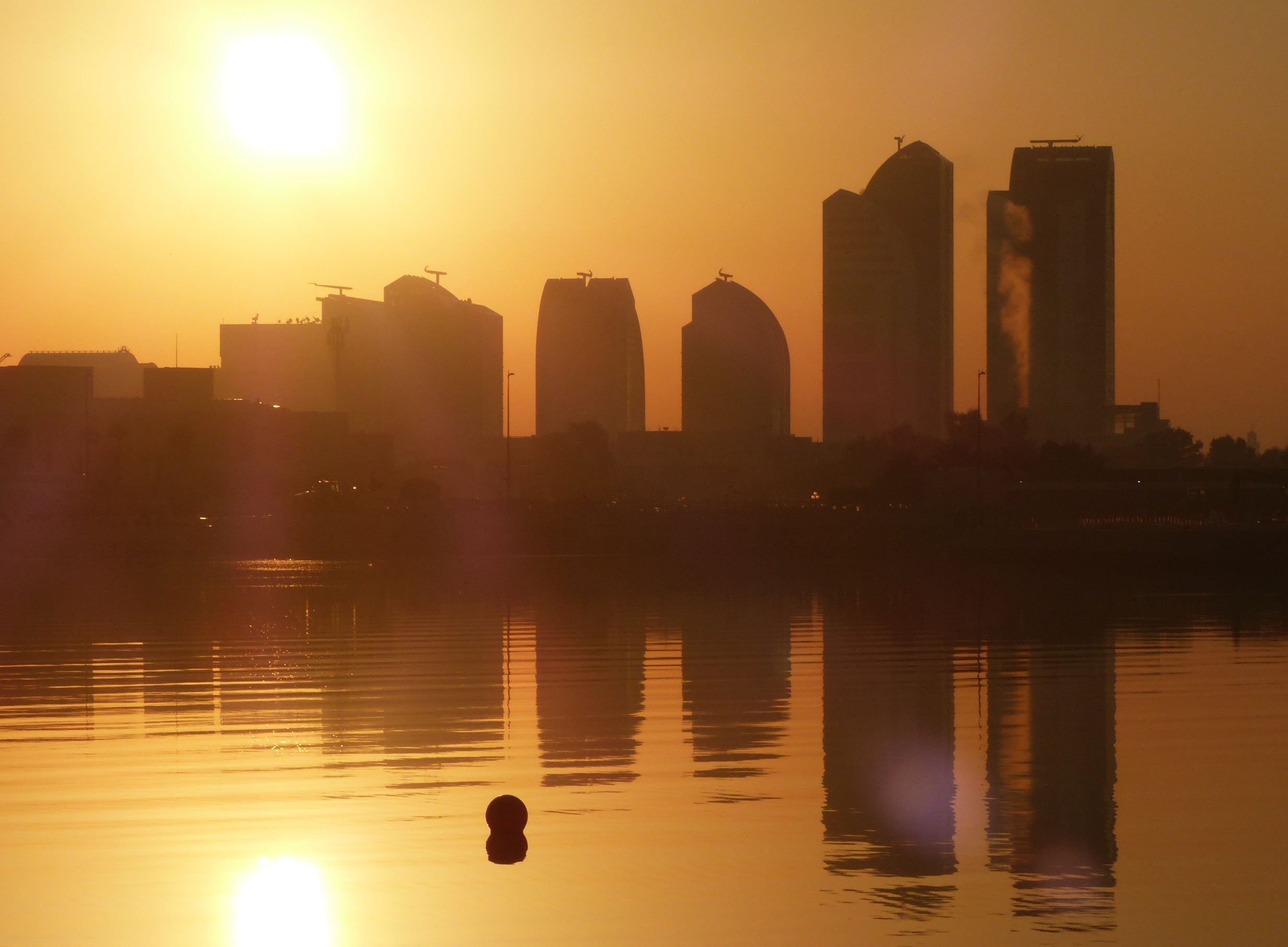 Tall buildings in mist with orange sky, reflected in water