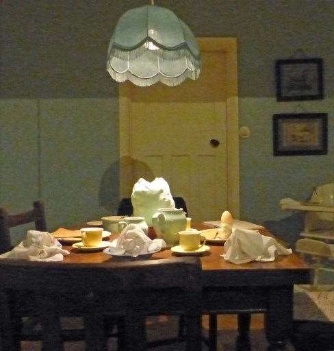 Old-fashioned kitchen table with teapot, cups and saucers