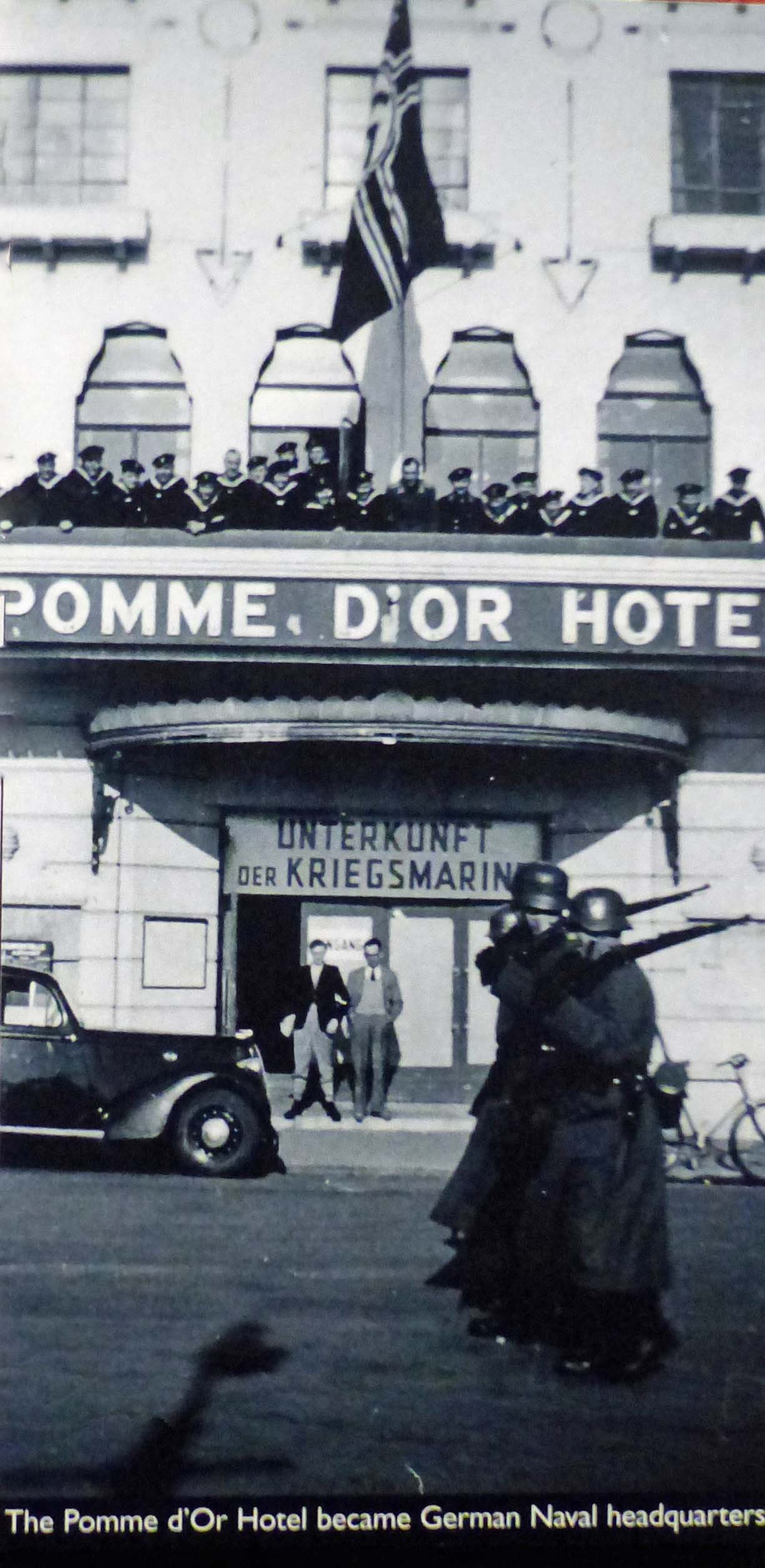 Black and white old photo of a hotel with flags