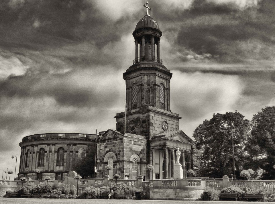Sepia photo of a church with dramatic sky