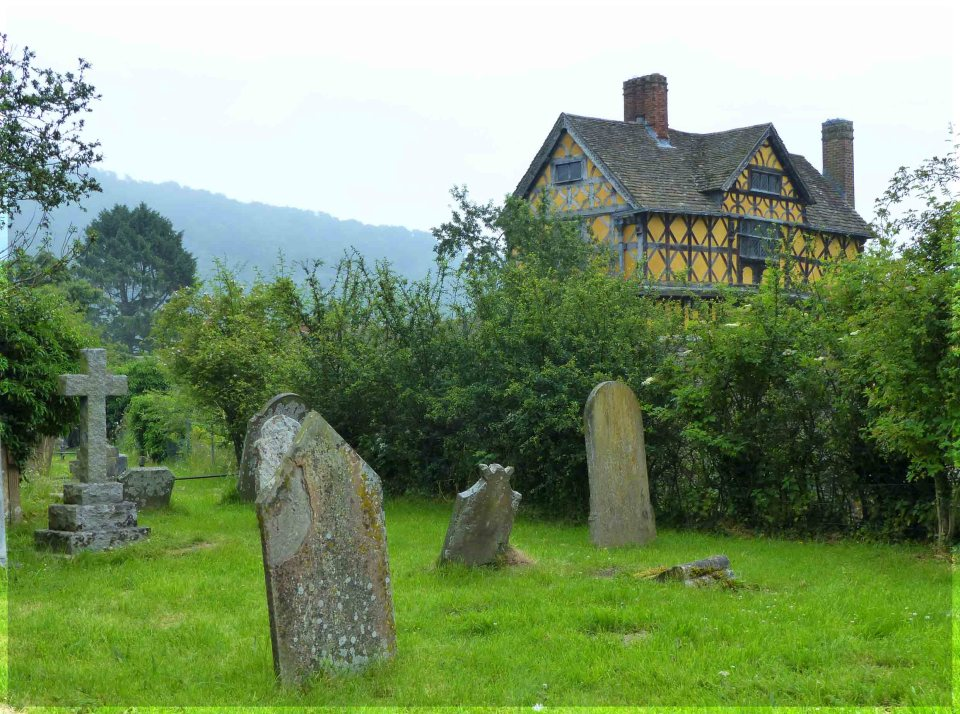 Yellow half-timbered house beyond a hedge with gravestones in front