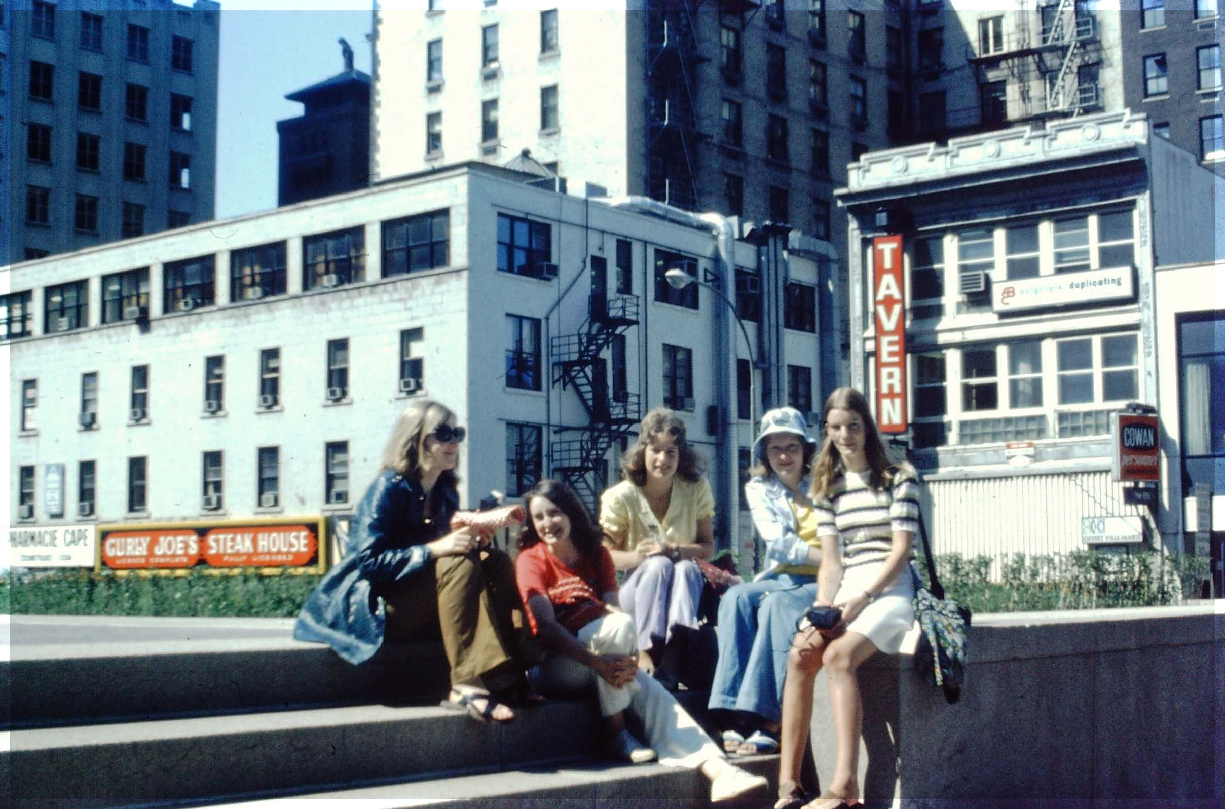 Five teenage girls sitting on steps in a city