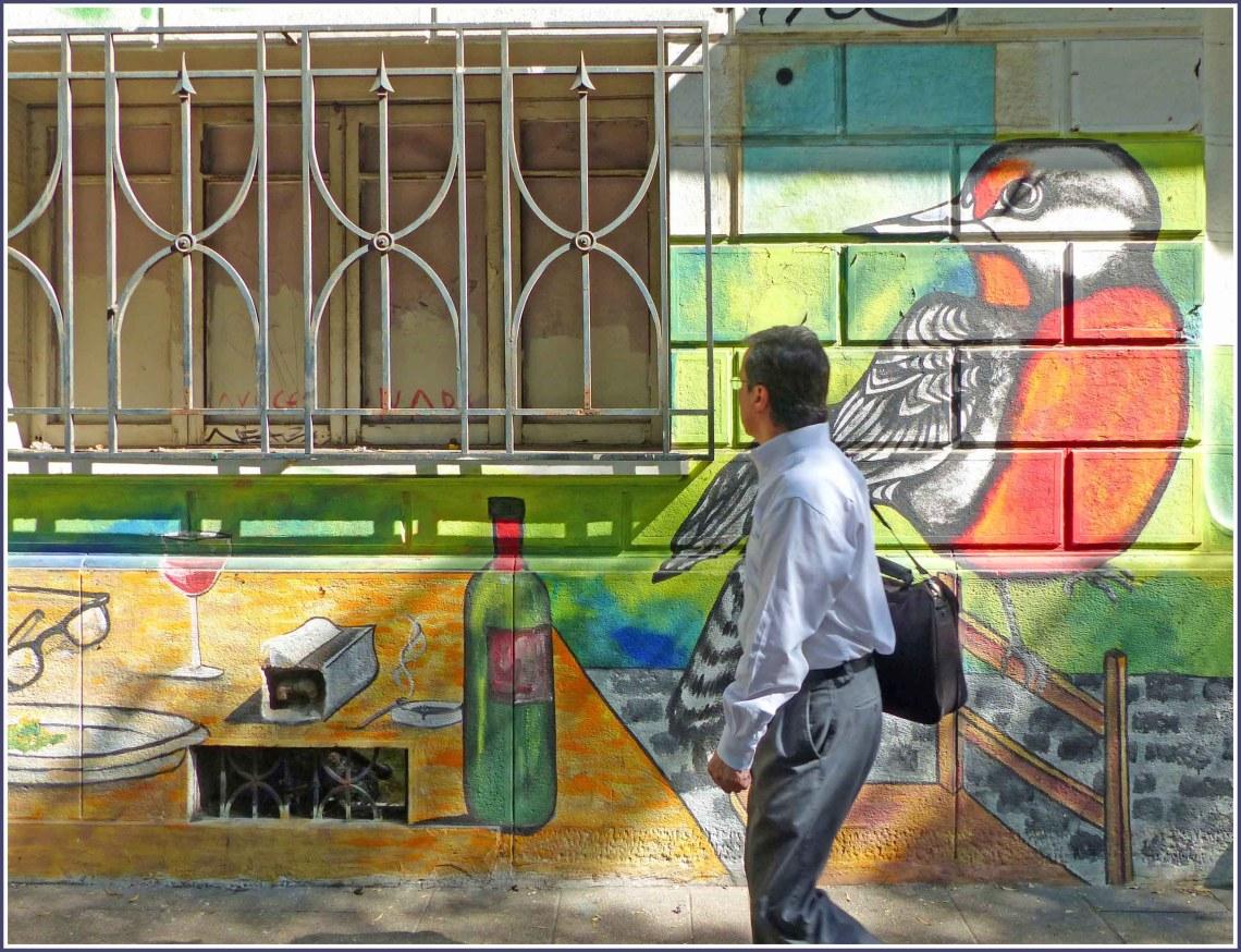 Man passing wall painting of orange bird
