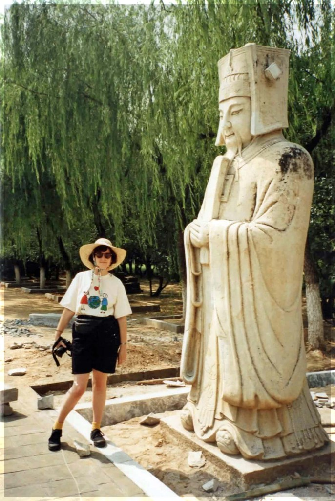 Woman standing by large statue